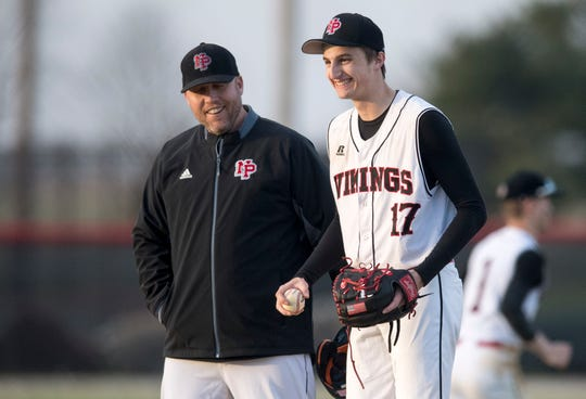 North Posey's Head Coach Jesse Simmons, left, and North Posey's Shane Harris (17)  laugh on the mound during the North Posey Vikings vs South Spencer Rebels game at North Posey High School Monday, April 1, 2019.