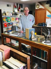 Kevin Garn stands by his showcase of rare and first edition books inside Ink & Quill Books, 236 W. Water Street in Oak Harbor. Ando Antiques and Collectibles shares the space.