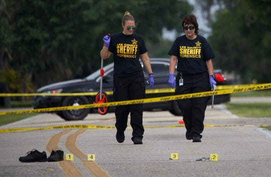 Crime scene investigators with the Lee Sheriff's department inspect the scene of a shooting in Fort Myers near Tropic Avenue and First Street.