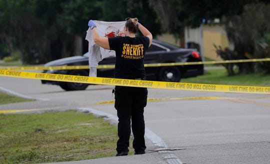 A crime scene investigator with the Lee County Sheriffs Office inspects a bloody shirt found near the scene of a homicide in the Fort Myers Shores area near Tropic Avenue and First Street Tuesday morning, April 2, 2019. The man died from his wounds.