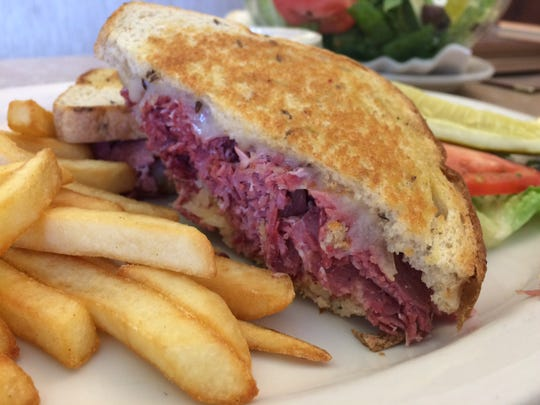 A Reuben sandwich with fries and a pickle from The Cafe in Cape Coral.