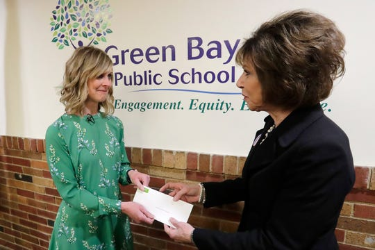 Shopko Public Relations Manager Michelle Hansen (left) hands a check for $200,000 to Green Bay Public Schools Superintendent Michelle Langenfeld on Tuesday. Hansen spent the week delivering $2.5 million to Green Bay area nonprofits as the company wound down its charitable foundation.