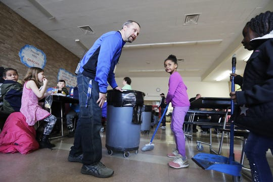 Sullivan Elementary's Micah Bootz, finalist for the Cintas' Custodian of the Year award, gets some help from first graders in the lunchroom on March 27 in Green Bay.