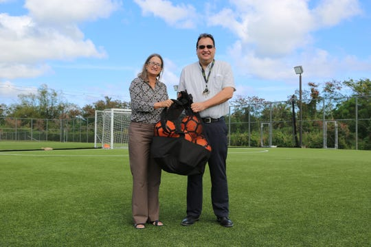 Guam Football Association Executive Director Cheri Stewart presents 10 soccer balls to Academy of Our Lady of Guam Athletic Director Tim Nelson in a short presentation event Thursday at the Guam Football Association National Training Center.