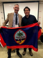 Andrew Gumataotao holds up the Guam flag with Harvard Professor of History Philip Deloria at the Conference for International History.
