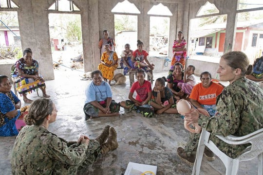 "U.S. Navy Lt. Cmdr. Erika Schilling, left, and Lt. j.g. Natalie Spritzer teach a ""helping babies breathe"" class to local Chuukese women and girls during Pacific Partnership 2019 in Chuuk March 31."