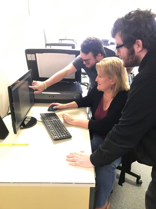 Susannah Ural, director of Civil War Governors of Mississippi Project, center, examines a Civil War letter, with other project helpers, Josh Vaughan, front, and Billy Loper, back.