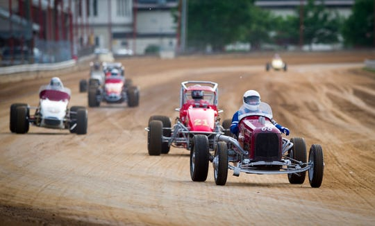 Vintage race cars make their way down the front straightaway as they make parade laps around the course before the races. Drivers competed on the mile-long track at the Indiana State Fairgrounds in the USAC Silver Crown 62nd running of the Hoosier Hundred, Thursday, May 26, 2016.