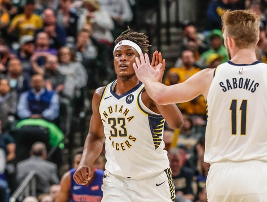 Indiana Pacers center Myles Turner (33) gets a high five from teammate Indiana Pacers forward Domantas Sabonis (11), after hitting a basket during a game between the Indiana Pacers and the Detroit Pistons at Bankers Life Fieldhouse on Monday, April 1, 2019.