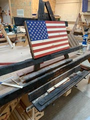 A flag in the process of being built rests on a stand at the Rustic Flag Company.