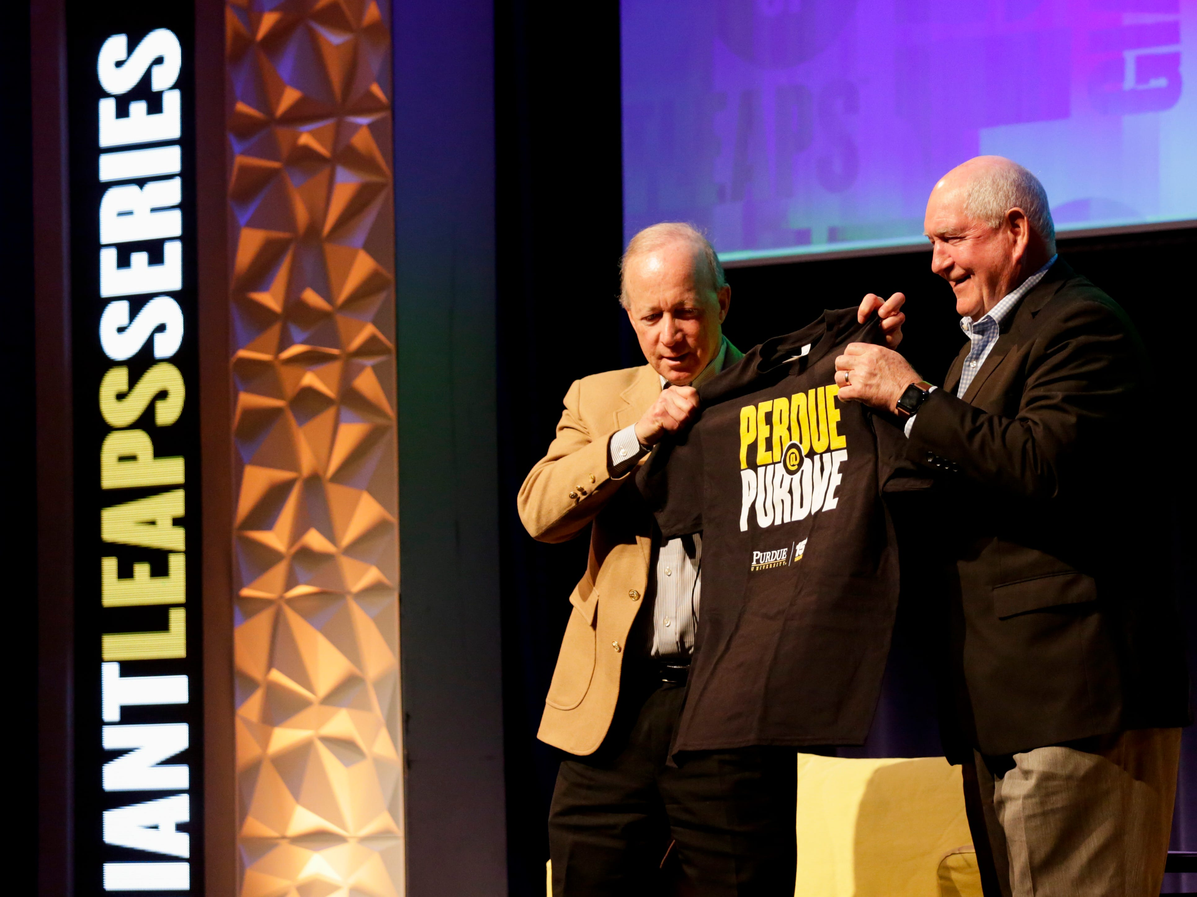 Purdue University president Mitch Daniels presents  U.S. Secretary of Agriculture Sonny Perdue with a t-shirt after speaking with him at an Ag Week Q&A conversation, Tuesday, April 2, 2019, at Purdue University in West Lafayette.