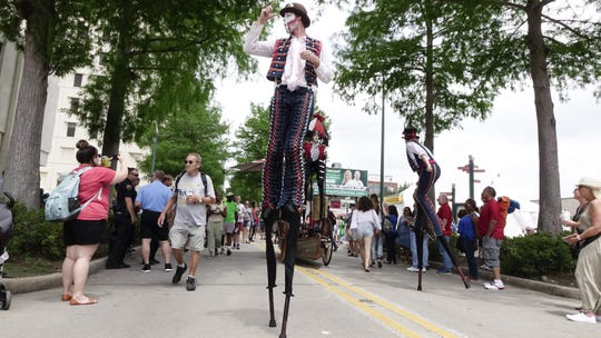Stilt performers makew their way down Jefferson Street during Festival International de Louisiane in downtown Lafayette Sat., April 29, 2017.