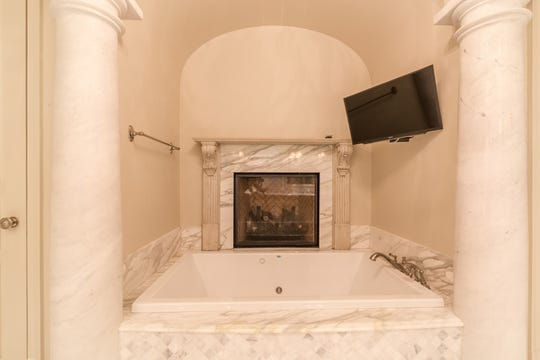 The marble tub includes a personal TV and fireplace.