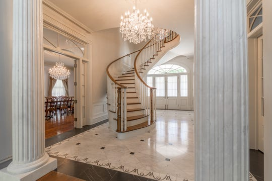 Stunning chandeliers and a grand staircase grace the home's entrance
