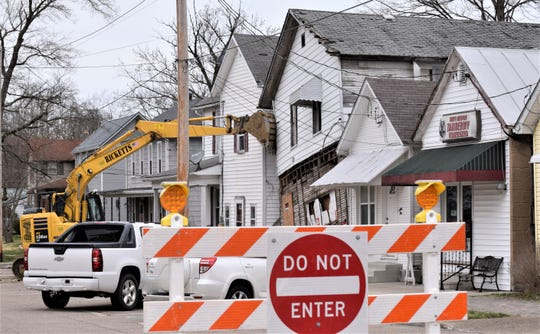 The view from the Canal and Center streets intersection on Tuesday in Carroll. A demolition crew began tearing down the structure at 63 W Canal St., in Carroll, Ohio. The building fell against the neighboring residence late Saturday night.