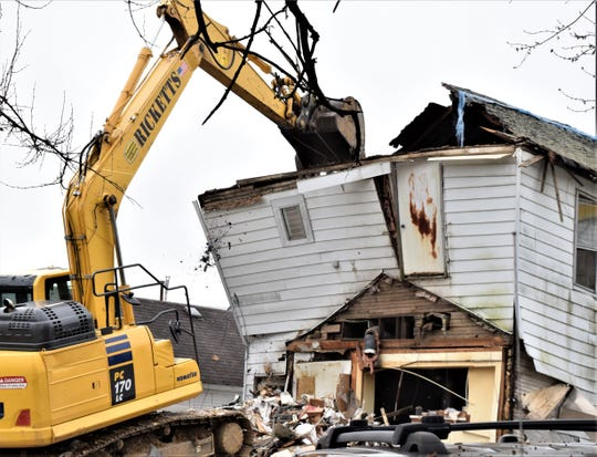 A demolition crew began tearing down the structure at 63 W Canal St., in Carroll, Ohio. The building fell against the neighboring residence late Saturday night.