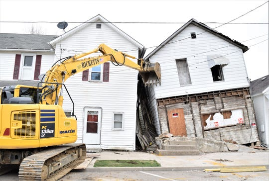 An excavator helps keep a collapsed structure from hitting the neighboring residence. A demolition crew began tearing down the structure at 63 W Canal St., in Carroll, Ohio. The building fell against the neighboring residence late Saturday night.