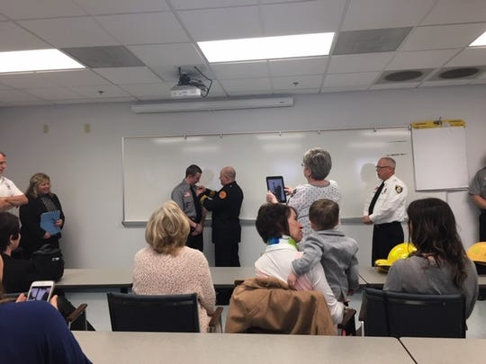 Ashland assistant fire Chief Dan Raudebaugh pins his son Benjamin's badge on him as Benjamin, 21, is sworn in as a Mansfield firefighter/EMT on Tuesday.
