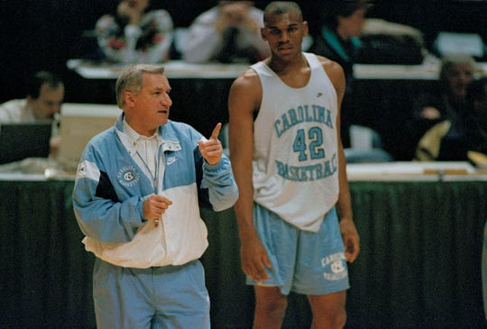 North Carolina basketball coach Dean Smith guides his team during practice as forward Jerry Stackhouse looks on, March 17, 1994. North Carolina meets Liberty University in Landover, Md. (AP Photo/Ted Mathias)