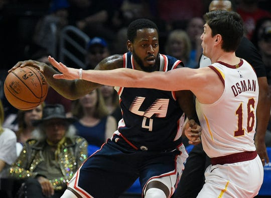 Los Angeles Clippers forward JaMychal Green, left, posts up against Cleveland Cavaliers forward Cedi Osman during the first half of an NBA basketball game in Los Angeles, Saturday, March 30, 2019. (AP Photo/Kelvin Kuo)