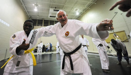In this 2011 archival photo, C.C. Wilkerson, 81, hands off his eyeglasses as he prepares to do some judo work with student Darrius Isom, 13. At the time, Wilkerson had been teaching judo at what is now the Ed Rice Community Center in Frayser for about 40 years.