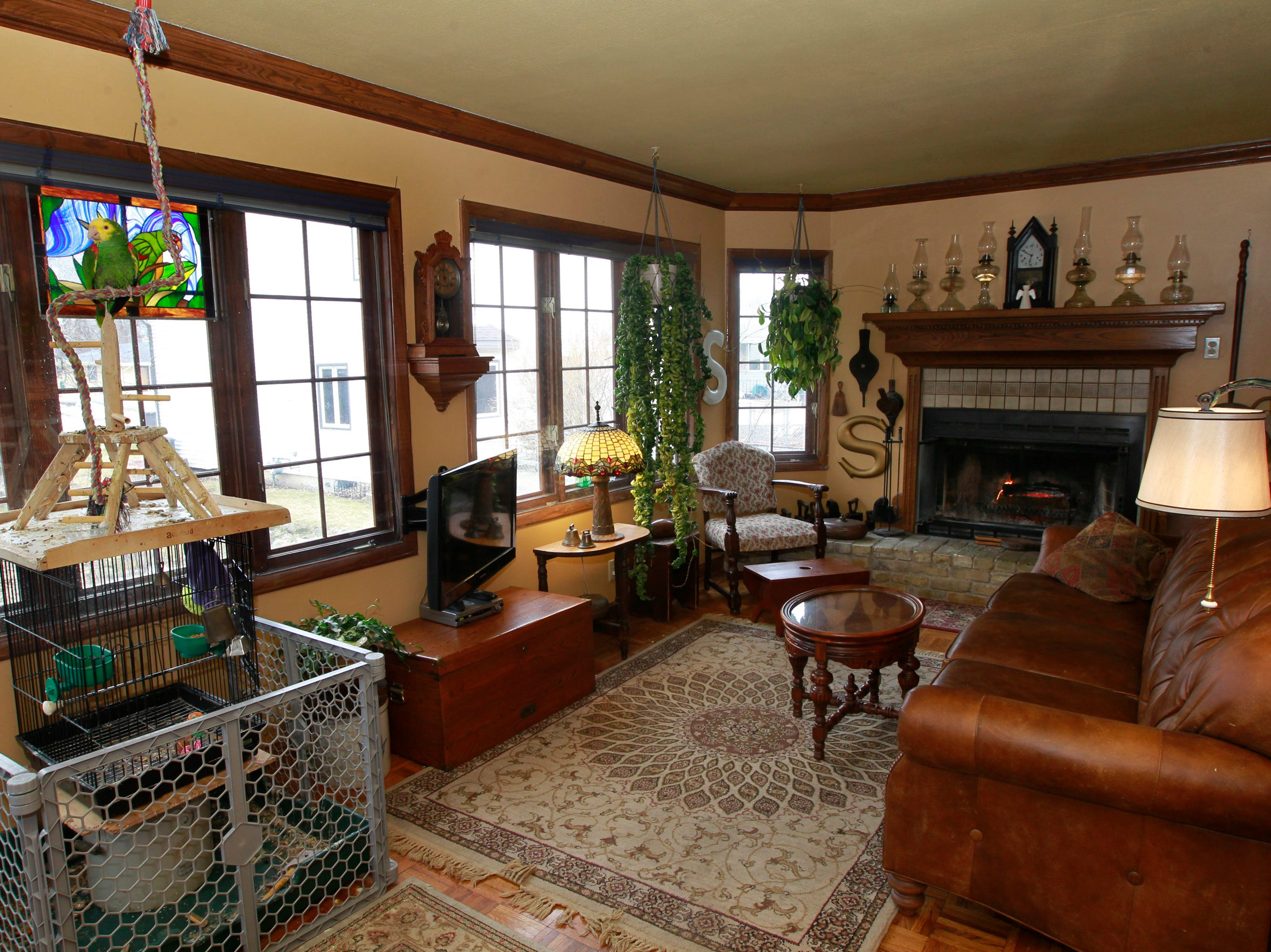 The sun room features a cozy fireplace and lots of natural light.  It is also the home for their talking pet parrot, Gerty.