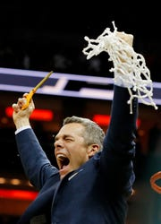 Virginia coach Tony Bennett celebrates after cutting down the net following his team's Elite Eight victory over Purdue on Saturday, March 30.