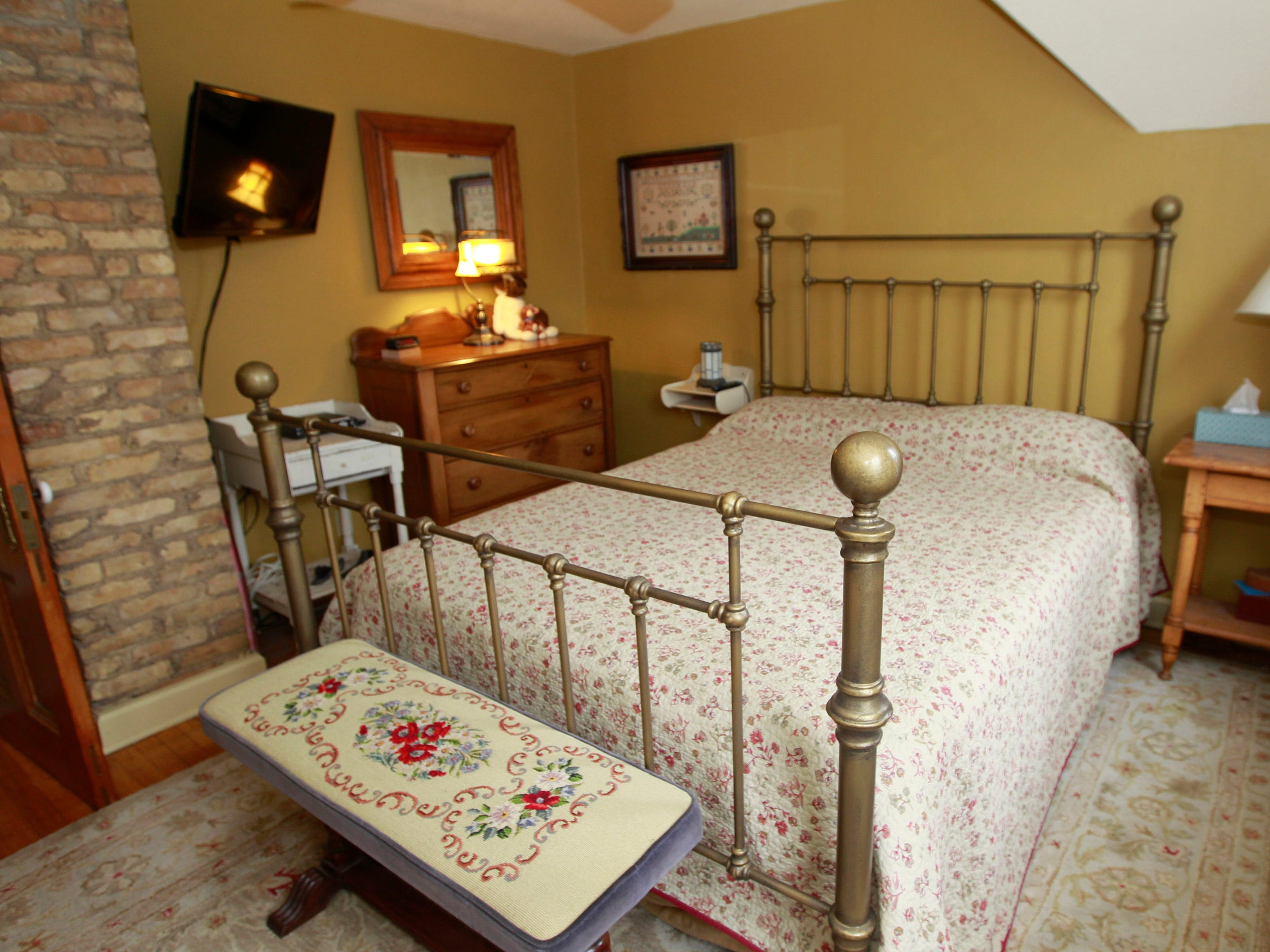 The master bedroom has cream city brick along with a brass bed.