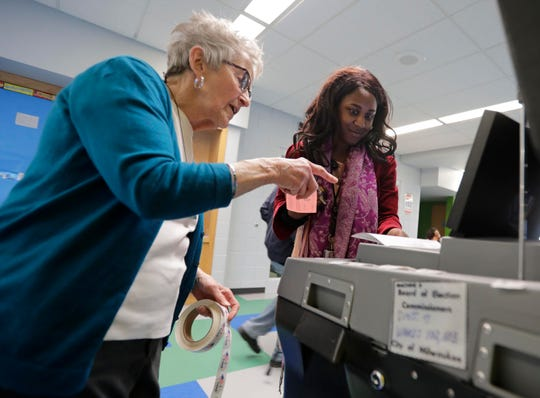 A poll worker helps a Milwaukee voter at the Sherman Park Boys & Girls Club.