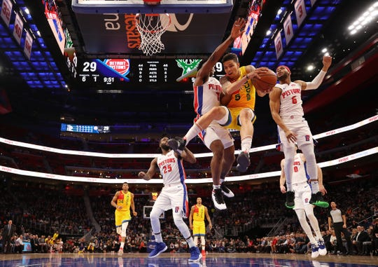 D.J. Wilson #5 of the Milwaukee Bucks battles for the ball with Bruce Brown and Stanley Johnson #7 of the Detroit Pistons during the first half at Little Caesars Arena on December 17, 2018 in Detroit, Michigan.