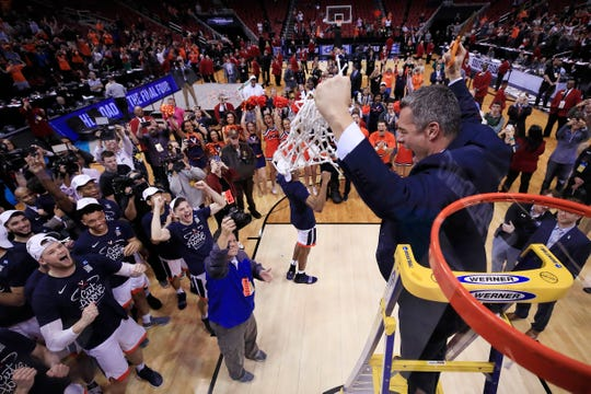 Virginia head coach Tony Bennett celebrates after cutting down the net following the Cavaliers' victory over Purdue in the South Region final Saturday in Louisville, Ky.