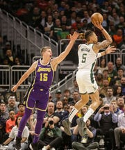 Milwaukee Bucks' D.J. Wilson(5) puts up a shot against the Los Angeles Lakers' Moritz Wagner during the first half of an NBA basketball game Tuesday, March 19, 2019, in Milwaukee.
