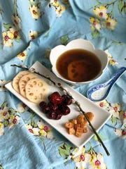Sliced lotus root, red dates and dried scallops are key ingredients in this chicken-based soup.