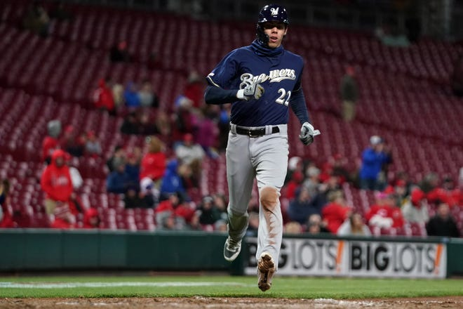 Christian Yelich scores on Ryan Braun's double in the ninth inning of a sparsely attended Monday night game at frigid Great American Ball Park.