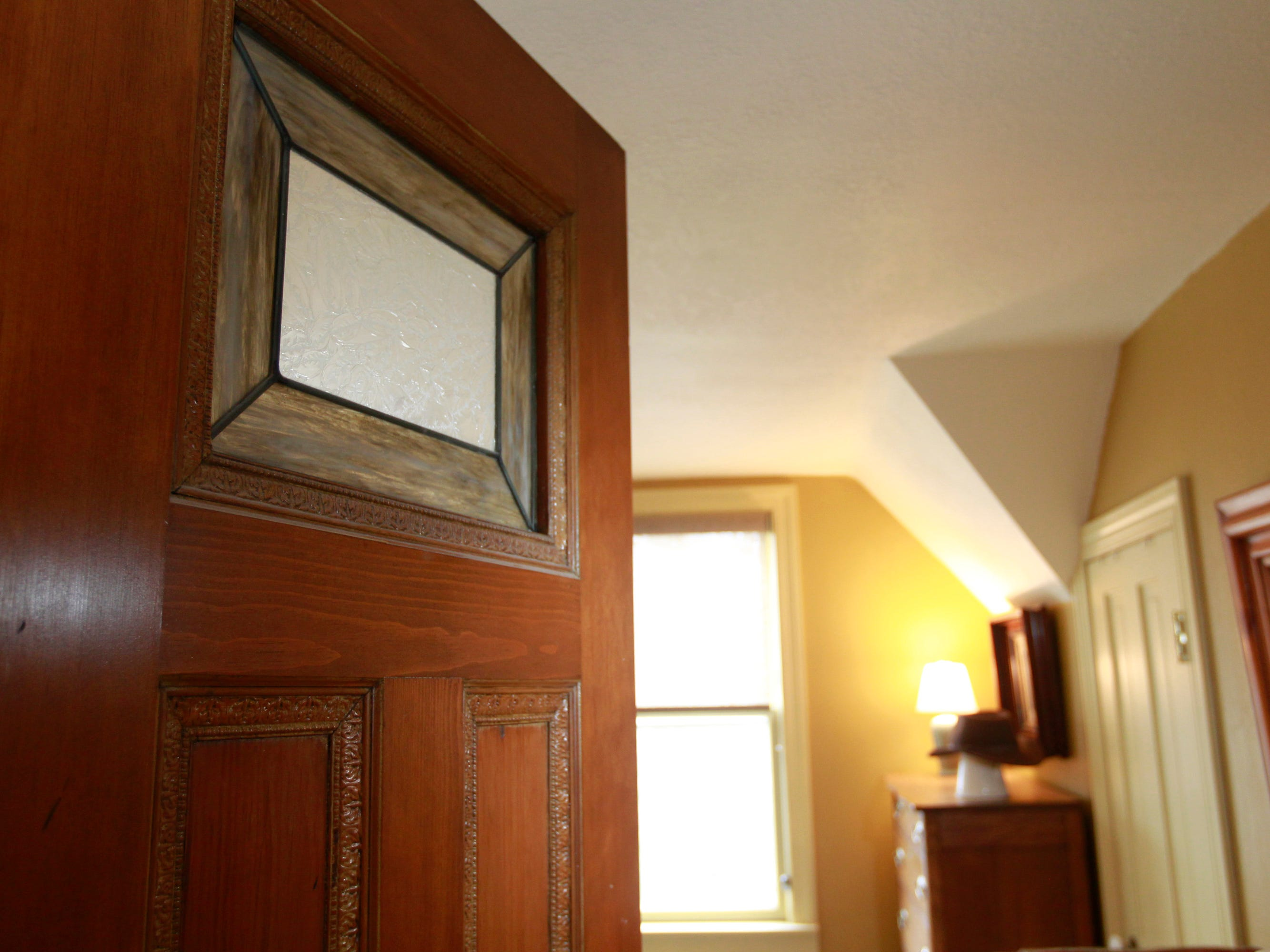 The bedroom door of the master bedroom has a stained glass feature.