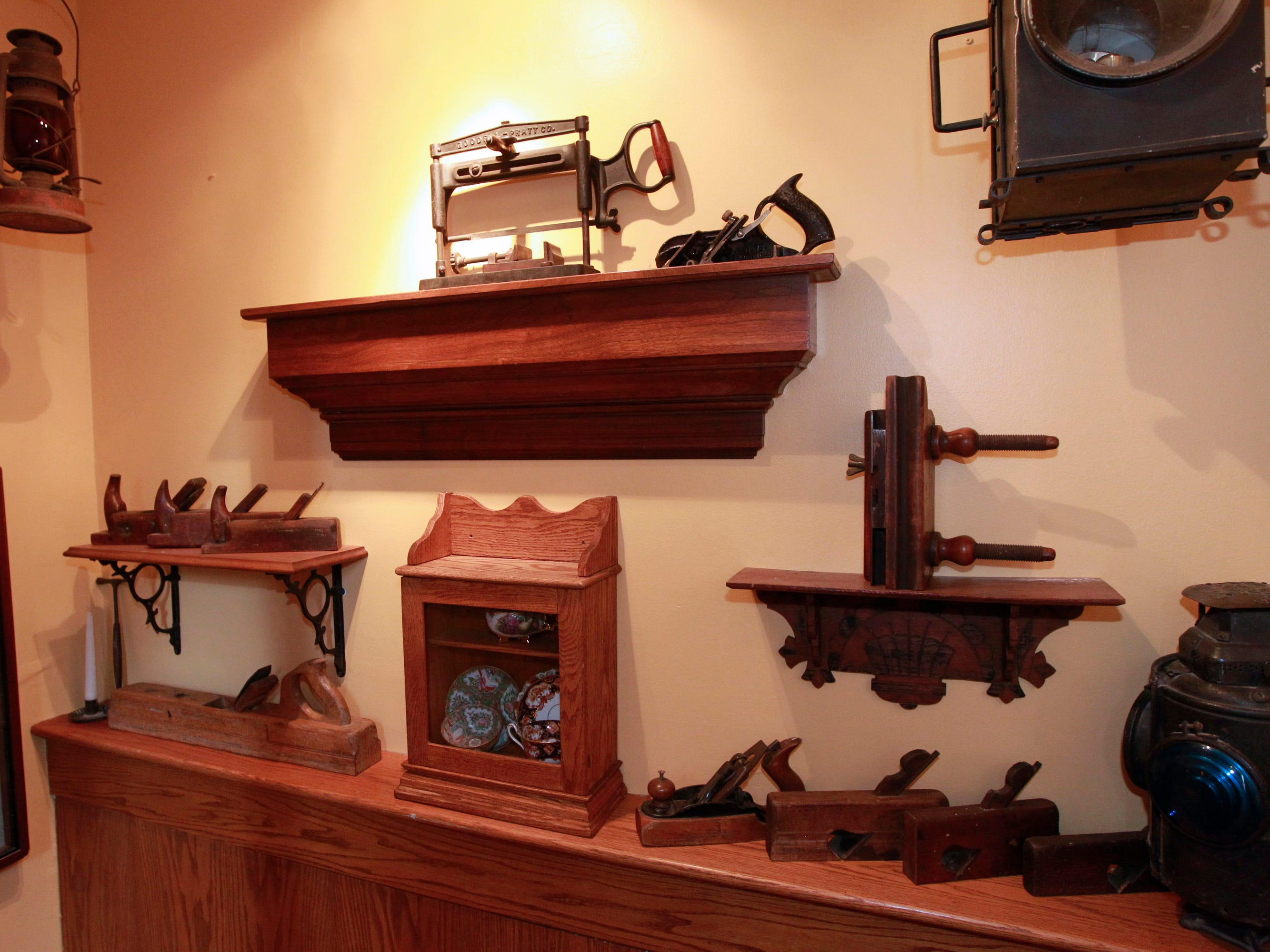 An assortment of antique pieces on display in the staircase area include a headlight from a steam train and wood planes used for shaving wood.