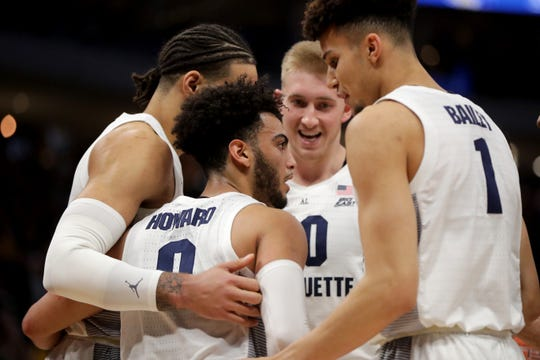 Marquette guard Markus Howard (0) gathers his teammates after being fouled during the first half of their game against Georgetown, March 9, at Fiserv Forum
