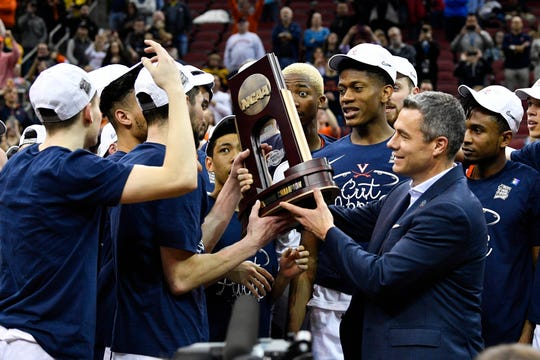 Virginia head coach Tony Bennett holds the regional championship trophy after the Cavaliers beat Purdue on Saturday in Louisville, Ky.
