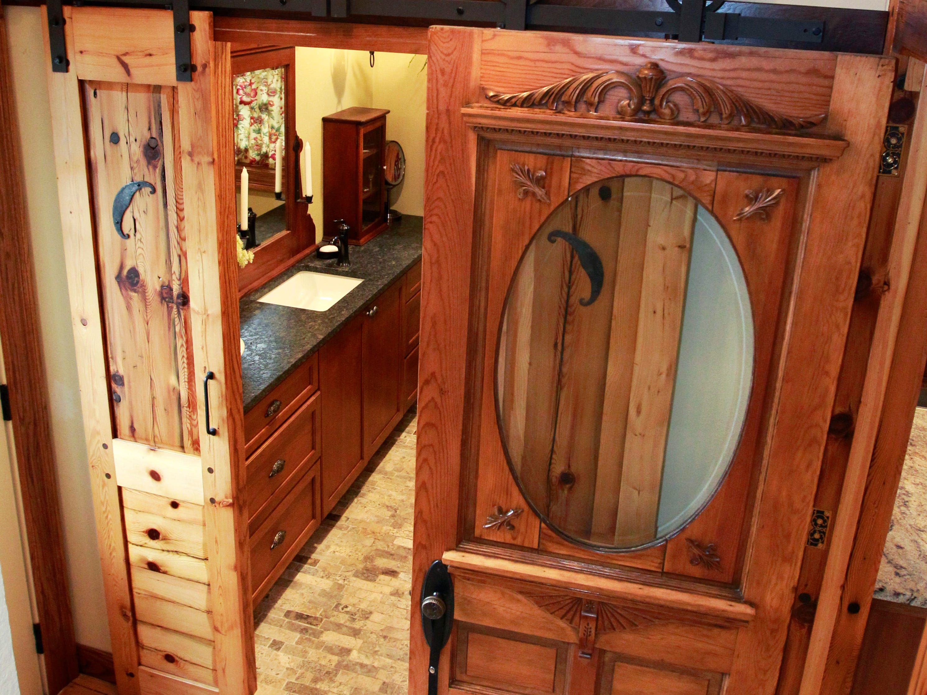 An Eastlake Victorian door (right) is seen along with a barn door leading into the downstairs bathroom.