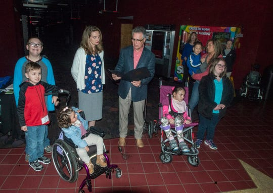 """Prattville Mayor Bill Gillespie Jr. reads a proclamation from the city with Autauga District Judge Joy Booth, who serves as the chair of the Autauga County Children's Policy Council. Children with autism were treated to a sensory-friendly version of the animated film """"Wonder Park"""" on Tuesday, April 2, 2019, at New Vision Theatre at Promenade 12 in Prattville, Ala."""