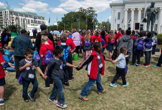 Students hold hands as they make their way through the crowd during the Child Advocacy Day event on the South Lawn of the Alabama State Capitol in Montgomery, Ala., on Tuesday, April 2, 2019.