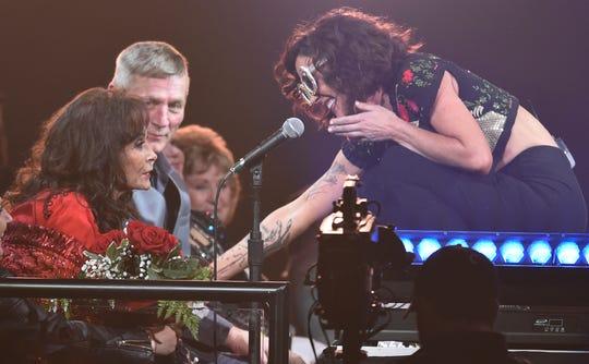 Amanda Shires, right, presents Loretta Lynn with flowers during the Loretta Lynn: An All-Star Birthday Celebration Concert at Bridgestone Arena on April 1, 2019.