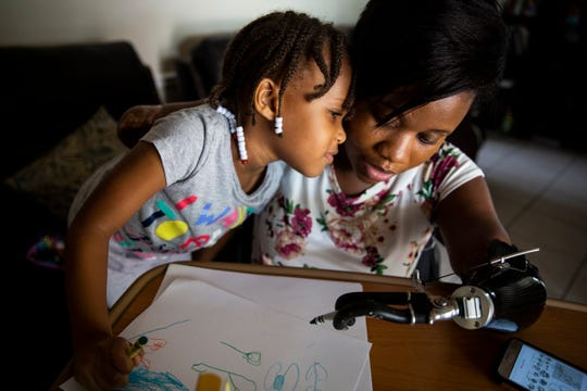 Aaliyah Ferguson-Walker, 4, leans on her mother, Kayleigh Ferguson-Walker, while they draw with crayons at Kayleigh's parents' home in Coral Springs on Saturday, November 17, 2018. In March of 2017, Kayleigh contracted sepsis, which caused her to lose her unborn child and all four of her limbs. Since then, she has been learning to complete tasks that have allowed her to slowly regain a level of independence, as well as learning how to fill her role as a mother in a different capacity.