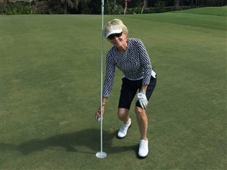 Bonita Bay Club member Terry Wells picks up the ball out of the hole on her third hole-in-one in nine days on No. 8 of the Marsh Course at Bonita Bay Club on Monday, Feb. 25, 2019.