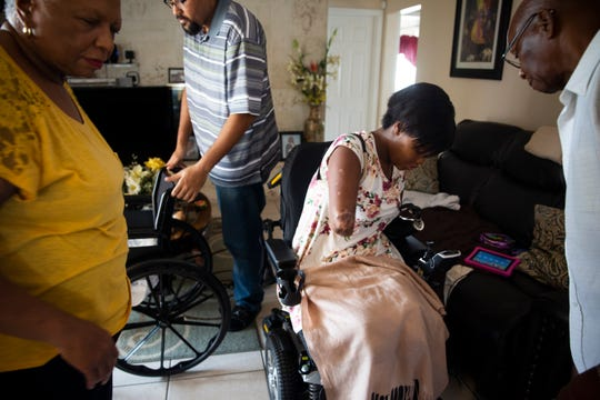 Kayleigh Ferguson-Walker's parents, Laurel Robinson, left, and Charles Robinson, right, and her husband Ramon Ferguson-Walker, center, help her transfer from a manual wheelchair to an electric one at her parents' home in Coral Springs on Saturday, November 17, 2018. Kayleigh's electric wheelchair offers her far more mobility because she is able to control the joystick with her prosthetic arm.