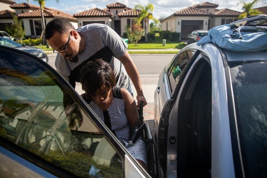 Ramon helps Kayleigh into the car at their home in Ave Maria on Saturday, January 12, 2019. The couple's house, reflected in the window of the car, is two stories tall and not very accessible for Kayleigh, who is unable to get up the stairs without being carried. Ramon and Kayleigh plan to build a new home in Ave Maria that will be ADA compliant.