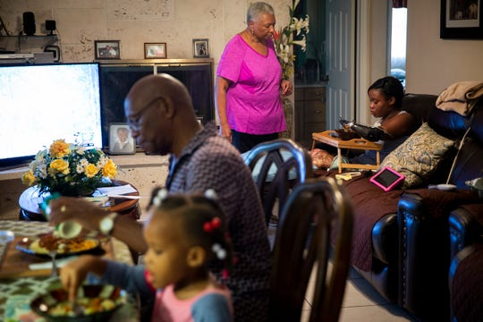 Charles and Aaliyah eat dinner at the table while Laurel gives Kayleigh her bowl of spaghetti as she sits on the couch at home in Coral Springs on Monday, December 10, 2018. The dining room and living room used to be set up in a way that kept the areas more separate, but Kayleigh's parents rearranged the furniture to give her more mobility.