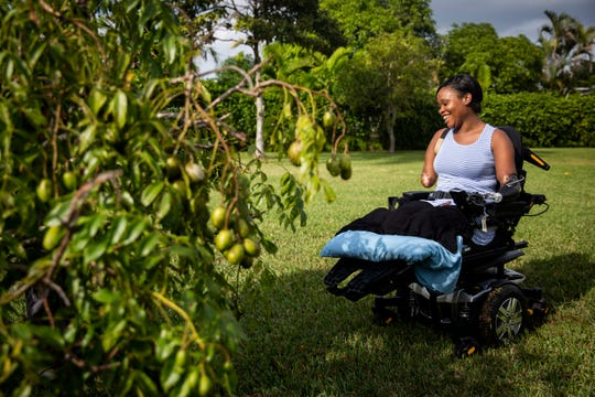 Kayleigh laughs as she sits in the sun next to a June plum tree in her parents' backyard in Coral Springs on Monday, December 10, 2018. Kayleigh still struggles with grief and daily frustrations, but she tries to stay positive, and has continued to make progress with the help of her family and her faith.