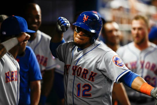 New York Mets' Juan Lagares (12) celebrates in the dugout after scoring during the seventh inning of a baseball game against the Miami Marlins, Monday, April 1, 2019, in Miami. (AP Photo/Brynn Anderson)
