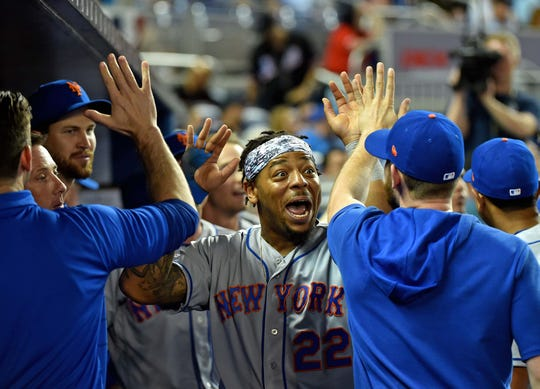 Apr 1, 2019; Miami, FL, USA; New York Mets pinch hitter Dominic Smith (22) celebrates with teammates after scoring a run in the ninth inning against the Miami Marlins at Marlins Park. Mandatory Credit: Steve Mitchell-USA TODAY Sports